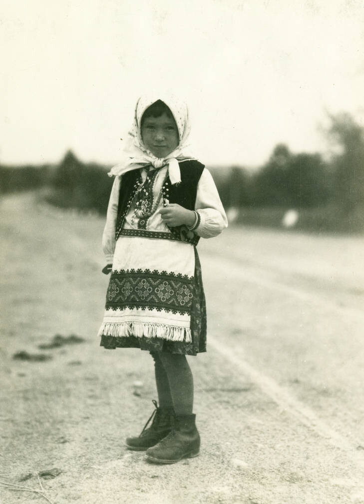 4.3 miles from Stryj en route to Dolina. Little Ruthenians (Hucul) girl on the highway. 2.30 PM. Typical costume. Velvet jacket beaded on edge, linen blouse and apron. September 21, 1934